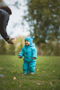 Happy family walking in autumn park: father and his little son - learn to stroll independently Royalty Free Stock Photo