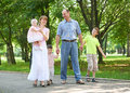 Happy family walking in city park, group of five people, summer season, child and parent