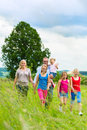 Happy family walking in the meadow with girls or daughters a summer Stock Photo