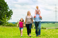 Happy family walking in the meadow with girls or daughters a summer Royalty Free Stock Photos