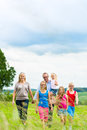 Happy family walking in the meadow with girls or daughters a summer Royalty Free Stock Image