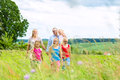 Happy family walking in the meadow with girls or daughters a summer Royalty Free Stock Images