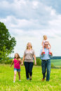 Happy family walking in the meadow with girls or daughters a summer Stock Image