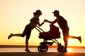 Happy family walking on sunset silhouettes of parents loving their child in a stroller Royalty Free Stock Images