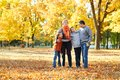 Happy family walks in autumn city park. Children and parents posing, smiling, playing and having fun. Bright yellow trees. Royalty Free Stock Photo
