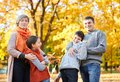 Happy family walks in autumn city park. Children and parents posing, smiling, playing and having fun. Bright yellow trees Royalty Free Stock Photo
