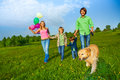 Happy family walks with balloons and dog in park Royalty Free Stock Photo