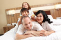 Happy family on white bed Stock Photos