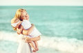 Happy family in white dress. Mother hugs baby in the sky Royalty Free Stock Photo