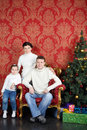 Happy family in white sweaters and jeans near christmas tree at home Stock Images