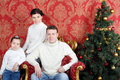 Happy family in white sweaters and jeans near christmas tree red room Royalty Free Stock Photography