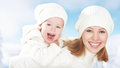Happy family on a winter walk mother and baby daughter in the white hats laughing Stock Images