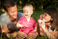 Happy family young beautiful couple lying on the grass in park with their one year old daughter and having fun Royalty Free Stock Image