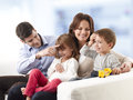 Happy family young sitting on sofa in living room Stock Images