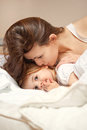 A happy family young woman and litle girl in bed Stock Photos