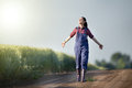 Happy farmer girl in wheat field walking beside green with stretched arms and enjoying the sun Stock Photos