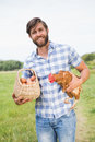 Happy farmer holding chicken and eggs