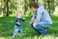 Happy father and baby boy son outdoor taking first steps Royalty Free Stock Photography