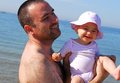 Happy father and baby daughter on the beach lifting his loved eleven months old healthy a sunny summer day Stock Photo