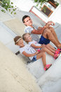 Happy father and cute daughters sitting on street in old greek town this image has attached release Royalty Free Stock Photography