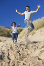 Happy Father and Daughter Jumping At Beach Stock Photography