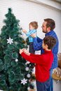A happy father and his sons decorate the Christmas tree at home, a happy childhood.