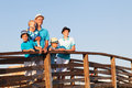 Happy father with his sons and little daughter standing on wooden bridge Royalty Free Stock Photo