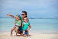 Happy father with his two daughters sitting on tropical beach vacation this image has attached release Royalty Free Stock Image