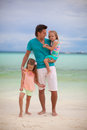 Happy father with his two daughters on tropical beach vacation this image has attached release Stock Photo