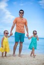 Happy father with his two daughters walking on tropical beach vacation this image has attached release Stock Photo