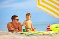 Happy father and kid playing on the beach toys Royalty Free Stock Photos