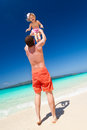 Happy father and little child on beach throwing his daughter in air at the tropical Stock Photos