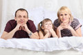 Happy father, little daughter and mother on white bed