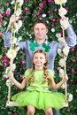 Happy father and little girl with shamrock on head on swing in garden next to verdant fence Royalty Free Stock Image
