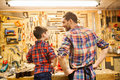 Happy father and little son workshop family carpentry woodwork people concept working with work tools wood planks at Royalty Free Stock Images