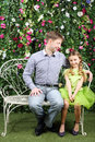 Happy father looks at little daughter sitting on retro bench white near verdant hedge Stock Image