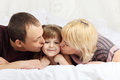 Happy father and mother lie on bed and kiss little white double daughter Stock Image