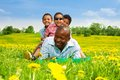 Happy father playing with boys smiling black african men sitting on his back laying in the spring park field yellow dandelions Stock Photos