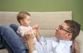 Happy father playing with cute baby in a sofa portrait of sitting over his belly at home Stock Photography