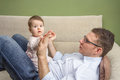 Happy father playing with cute baby in a sofa portrait of sitting over his belly at home Royalty Free Stock Photo
