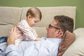 Happy father playing with cute baby in a sofa portrait of sitting over his belly at home Stock Photos