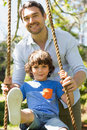 Happy father pushing boy on swing in playground Royalty Free Stock Image