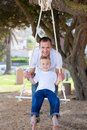 Happy father pushing his son on a swing Royalty Free Stock Photography