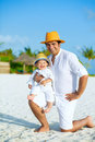 Happy father with son on the beach and panama hats and white clothes Stock Photo