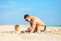 Happy father and son digging in sand on the beach Stock Photo