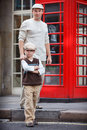 Happy father and son outdoors by red phone booth in city Royalty Free Stock Photo