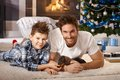 Happy father and son playing with puppy at xmas Royalty Free Stock Photo