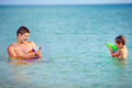 Happy father and son playing with water pistols in the sea Royalty Free Stock Photos