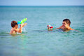 Happy father and son playing with water pistols in the sea Stock Photo