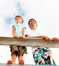 Happy father and son standing on a wooden railing Royalty Free Stock Images